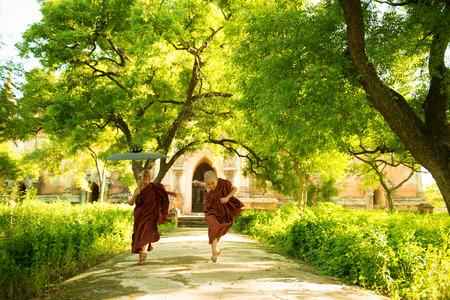 gente corriendo: Dos peque�os juguetones monjes novicios budistas que se ejecutan al aire libre bajo la sombra del �rbol verde, el monasterio de las afueras, Myanmar.