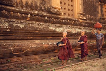 limosna: J�venes monjes novicios del Sudeste Asi�tico budistas caminando limosna ma�ana en Old Bagan, Myanmar Foto de archivo