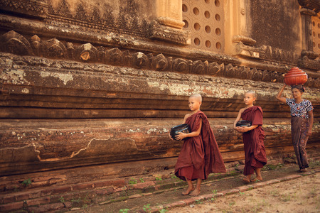 buddhist's: Southeast Asian young Buddhist novice monks walking morning alms in Old Bagan, Myanmar