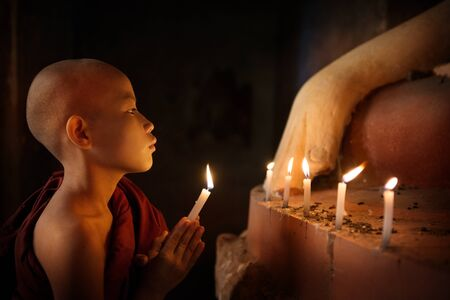 buddhism prayer belief: Portrait of young novice monk praying with candlelight inside a Buddhist temple, low light setting, Bagan, Myanmar.