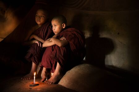 meditation man: Young novice monks lighting up candle light inside a Buddhist temple, Bagan, Myanmar.