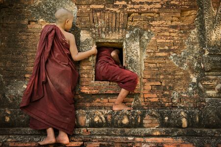 buddhist's: Two playful young novice monks climbing into Buddhist temple from window, Bagan, Myanmar. Stock Photo