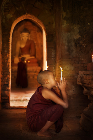 buddhist's: Portrait of young novice monks praying with candlelight inside a Buddhist temple, Bagan, Myanmar.