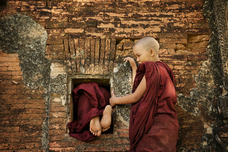 Playful young novice monks climbing into Buddhist temple from window, Bagan, Myanmar.