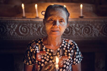 low light: Old wrinkled traditional Asian woman praying with candle light inside a temple, low light, Myanmar Stock Photo