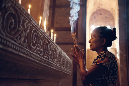 Old wrinkled traditional Asian woman praying with incense sticks inside a temple, low light, Myanmar