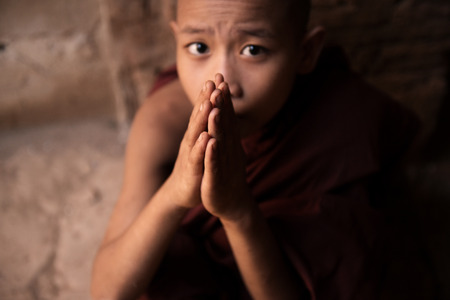buddhism prayer belief: Portrait of young novice monk praying inside ancient Buddhist temple, Bagan, Myanmar. Stock Photo