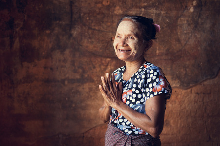 ethnic woman: Portrait of traditional Asian Burmese woman greeting, standing inside a temple, low light, Bagan, Myanmar