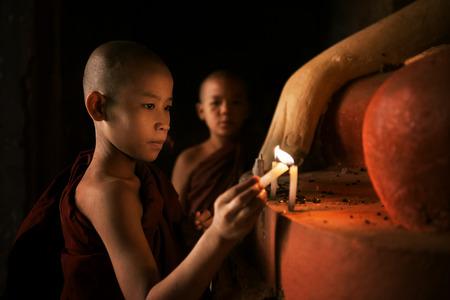 moine: Portrait de jeunes moines novices illuminant chandelles dans un temple bouddhiste, réglage de faible luminosité, Bagan. Banque d'images