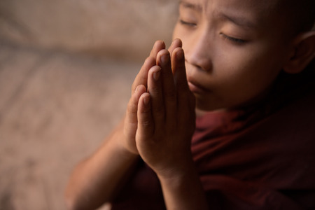 bless: Young novice monk praying inside Buddhist temple, Bagan, Myanmar.