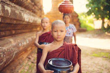 limosna: Monjes budistas del sudeste asi�tico j�venes caminando limosna ma�ana en Old Bagan, Myanmar Foto de archivo