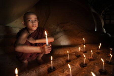 asian boy: Little novice monk hand holding candlelight inside temple, Bagan, Myanmar. Stock Photo