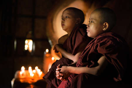buddhism prayer belief: Young novice monks sitting inside a Buddhist temple, Bagan, Myanmar.