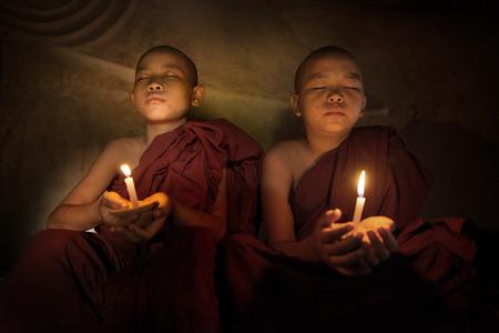 luz de velas: Pequeños monjes rezando con luz de las velas