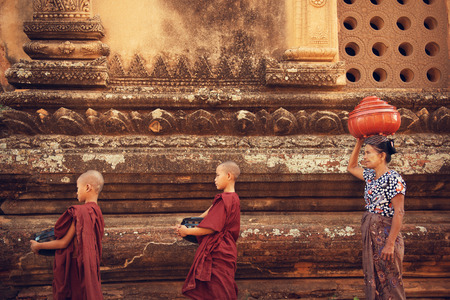 asia children: Buddhist novice monks walk to collect alms and offerings at old bagan, Myanmar. This procession is held every morning.