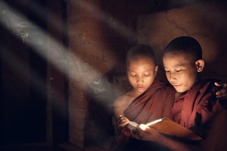 thru: Southeast Asian novice monk reading book inside monastery, beautiful natural light shining thru. Stock Photo
