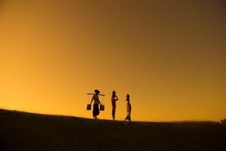 ollas de barro: Silueta de los grupos agricultores tradicionales asiáticos que llevan ollas de barro en la cabeza que van de regreso a casa, Bagan, Myanmar