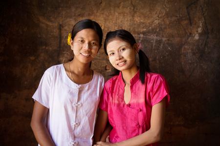 Portrait of two beautiful Myanmar girls smiling, low light inside a temple.