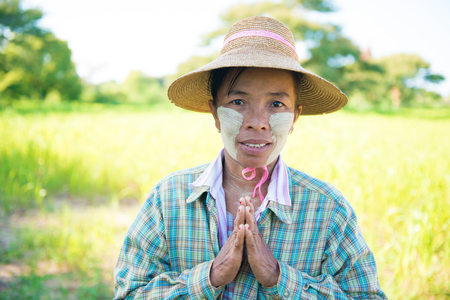 blessing: Portrait of a mature Burmese female farmer with thanaka powdered face in blessing gesture.