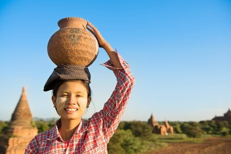 poverty: Portrait of Young Asian Burmese traditional female farmer carrying clay pot on head, Bagan, Myanmar