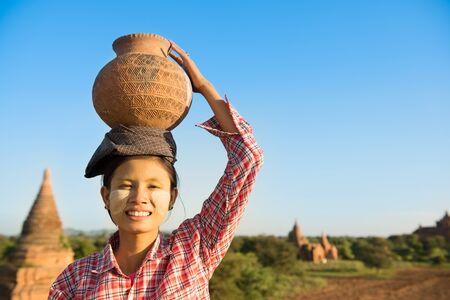 pobreza: Retrato de un agricultor femenina llevando la olla de Birmania asiática joven tradicional de barro en la cabeza, Bagan, Myanmar