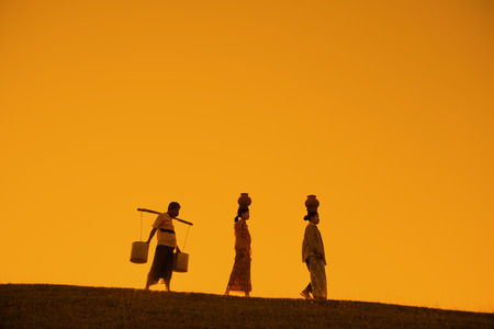 villager: Silhouette of Asian traditional farmers carrying clay pots on head going back home, Bagan, Myanmar