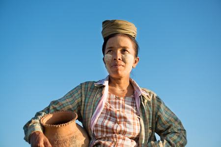 poverty: Portrait of mature Asian Burmese traditional female farmer carrying clay pot, Bagan, Myanmar