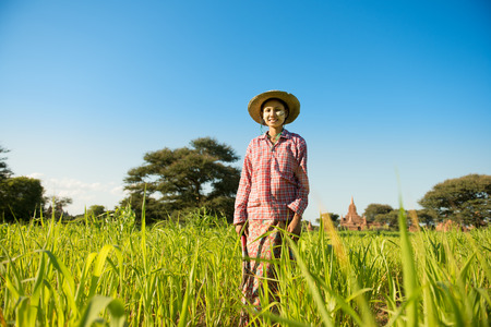 Portrait of a young Asian Myanmar farmer with thanaka powdered face standing in the farm field.