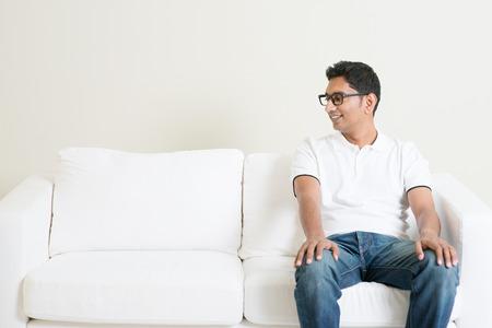 bonhomme blanc: Jeune homme indien seul assis sur le canap� seul et en regardant copie c�t� espace. Lifestyle homme asiatique � la maison. mod�le masculin Handsome.