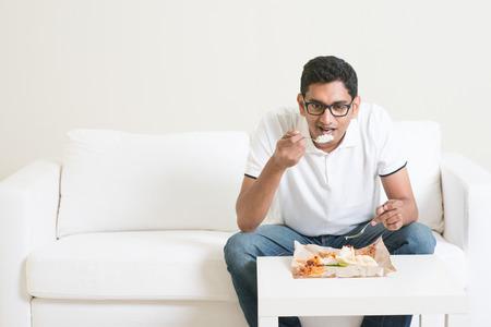 hombre comiendo: solo hombre indio joven que come alimentos por sí sola. Tener nasi lemak como el almuerzo. El estilo de vida de Asia chico en casa. Foto de archivo