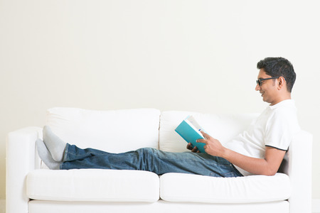 handsome young man: Young single Indian guy reading book and rest at home. Asian man relaxed on sofa indoor. Handsome male model. Stock Photo