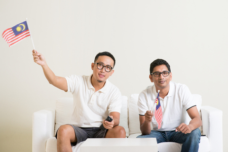 Young men watching live sport television program at home, waving Malaysia flag.