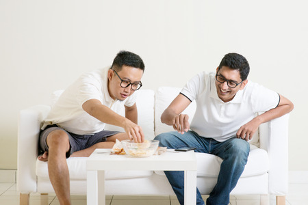 Men talk concept. Two young male friend gathering, chatting and eating at home. Multiracial people friendship.