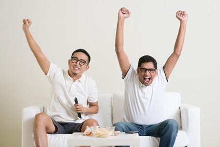 Vrolijke groep vrienden kijken voetbalwedstrijd op tv thuis. Stockfoto
