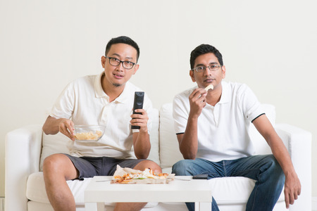 watching football: Group of friends sitting on sofa watching football match on television together at home. Stock Photo