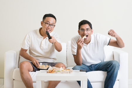food concept: Friendship, technology and home concept. Smiling male friends with remote control and junk food at home.