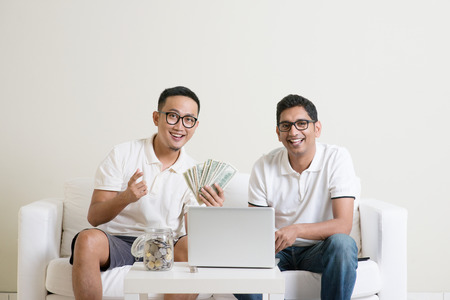 eBusiness concept. Young guys counting cash with partner, earning money from their successful online business. Asian men working from home.