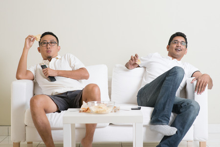 boy sitting: Male friends watching a movie at home. Stock Photo