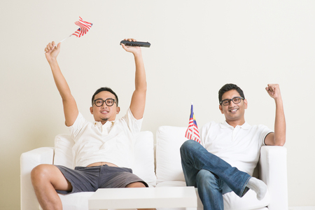 Young men watching live sport television program at home, waving Malaysia flag shouting and celebrate.