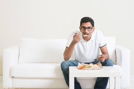Lonely young single Indian man eating food alone, copy space at side. Having nasi lemak as lunch. Lifestyle of Asian guy at home. Standard-Bild