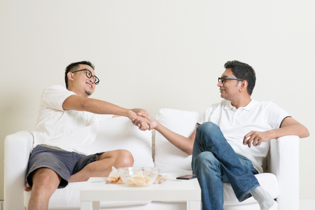 Man sitting on sofa and handshaking with friend at home. Multiracial people friendship.