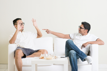 two men: Men arguing. Two young male friend having argument at home. Multiracial people friendship.