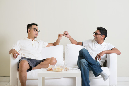 promises: Friends sitting on sofa and giving hand promise at home. Multiracial people friendship. Stock Photo