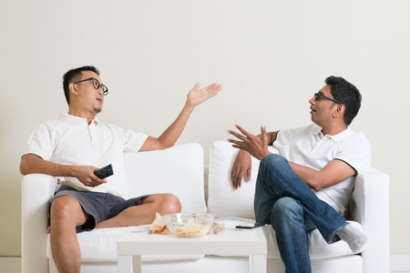 Men arguing. Two male friend disagree to each other and having argument at home. Multiracial people friendship. Archivio Fotografico