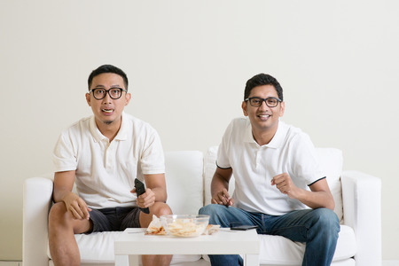 sports fans: Friendship, sports and entertainment concept. Male friends watching live sports show together on tv at home.