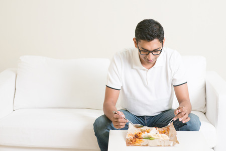 only man: Lonely single Asian Indian man eating food alone at home, copy space at side. Having nasi lemak as lunch. Stock Photo