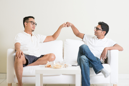 human fist: Man sitting on sofa and giving fist bump to friend at home. Multiracial people friendship. Stock Photo
