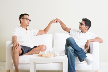 dva: Muž seděl na pohovce a dává pěstí ránu příteli doma. Mnohonárodnostní lidé přátelství.