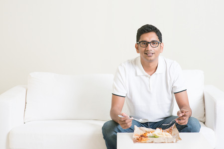 only man: Young single Indian man eating food alone, copy space at side. Having nasi lemak as lunch. Lifestyle of Asian guy at home.