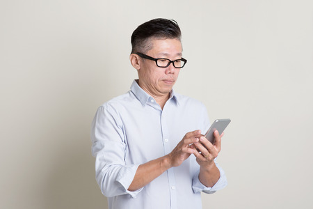 Portrait of single mature 50s Asian man in casual business playing smartphone, standing over plain background with shadow. Chinese senior male people. Stock Photo